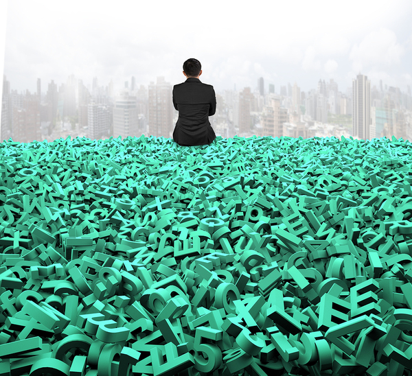 Man sitting on a pile of green letters looking at a city.