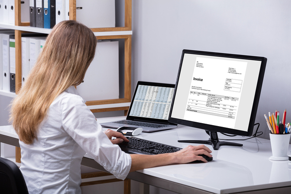 Woman working at a desk with a desktop computer.