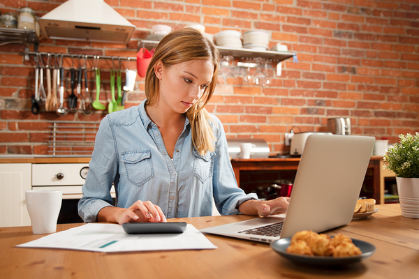 Woman working at a laptop in her kitchen.