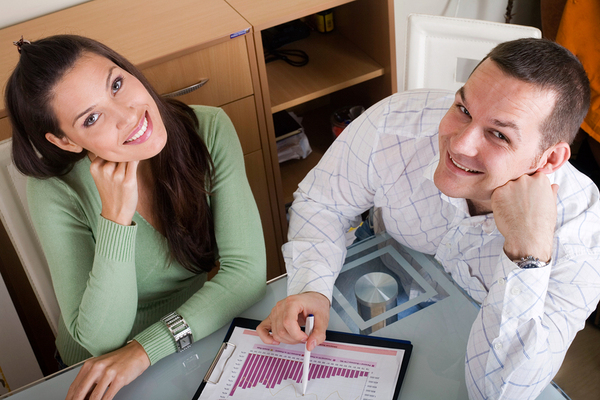 Two people smiling and looking at charts.