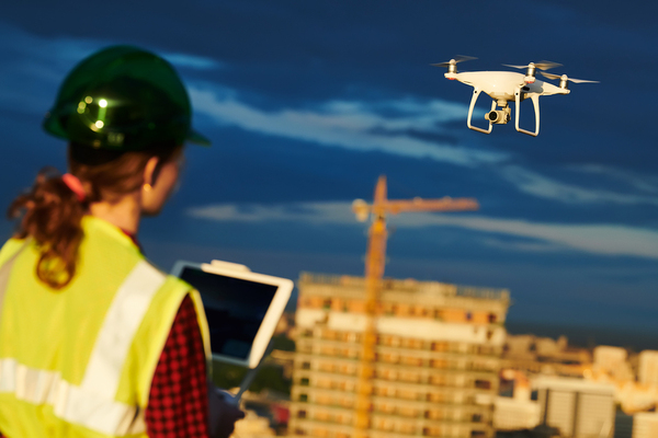Woman wearing a hardhat and yellow reflective vest flying a drone.