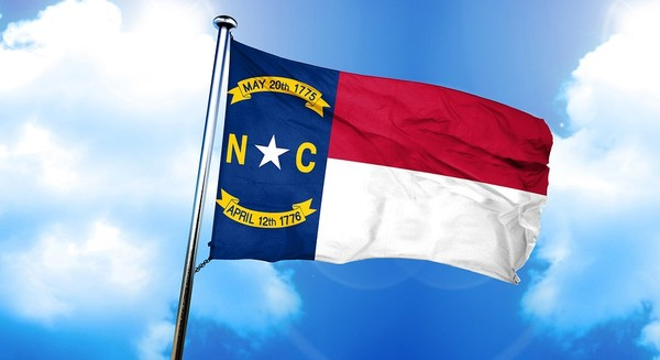 North Carolina flag flying with a blue sky in the background