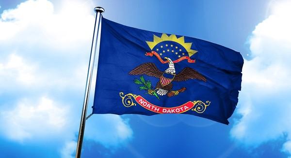 North Dakota flag flying with blue sky background