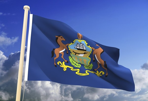 Pennsylvania state flag flying with blue sky in the background