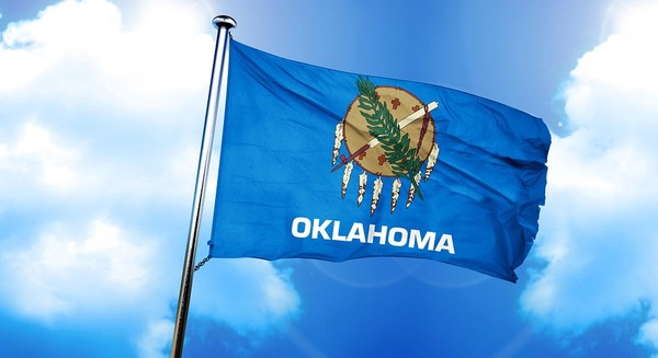 Oklahoma state flag flying with a blue sky in the background