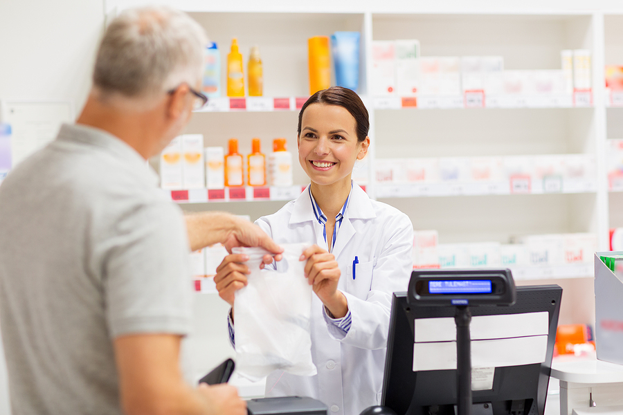 Pharmacist handing a filled prescription to a customer.