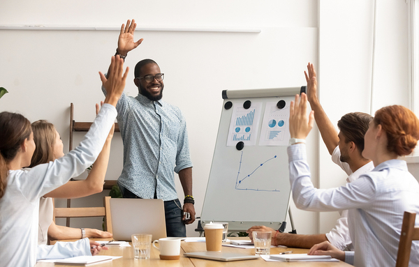 Group of colleagues around a conference table smiling and raising their hands.