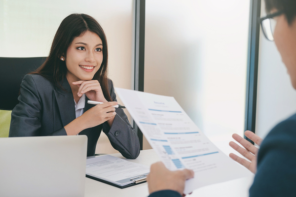 Smiling woman speaking with a job candidate.