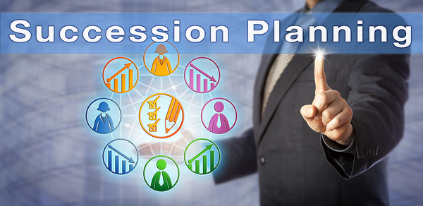 Man with a business suit pointing to the words Succession planning.