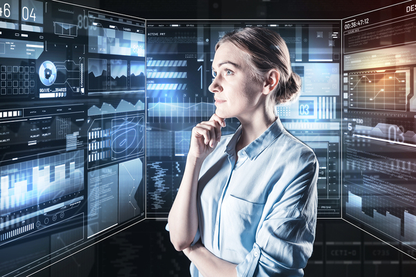 Woman looking at multiple screens with charges and graphs.