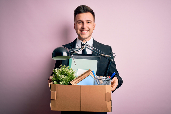 Smiling man holding a box filled with desk items.