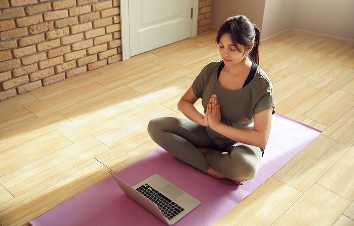 Woman sitting on the floor in a meditative position.