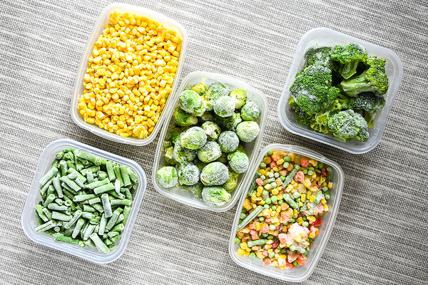 Plastic bowls filled with vegetables.