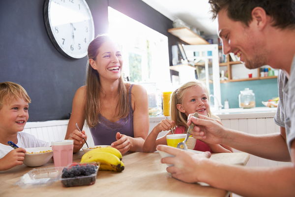 Family sitting down and eating breakfast smiling.