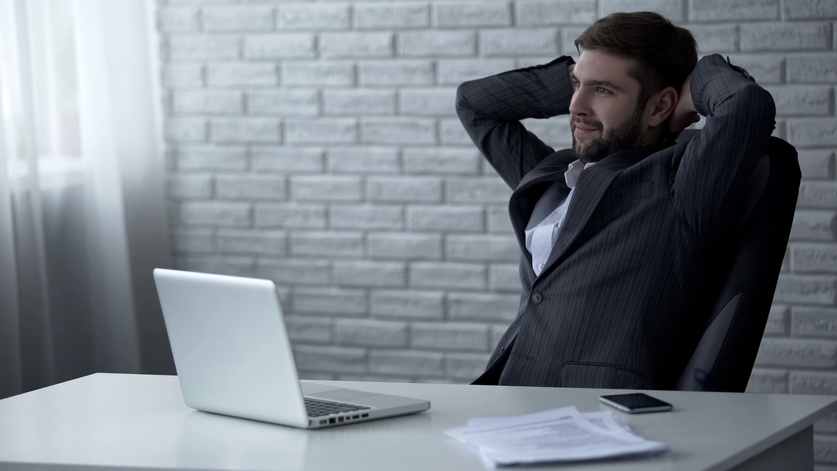 Sitting at a desk with hands behind head.