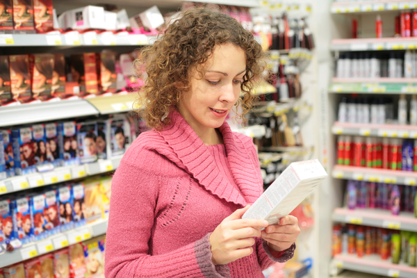Woman looking at a good package label in a grocery store.
