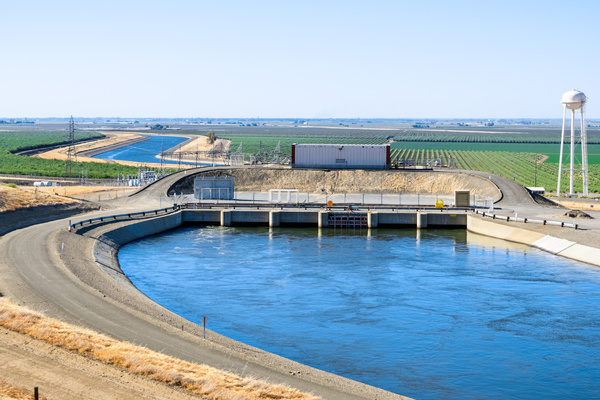 Dam with green fields in the background.