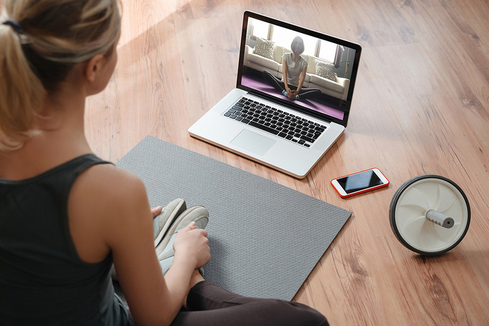 Woman performing online yoga using her laptop.
