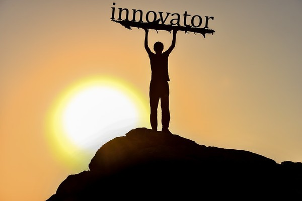 Person standing on a hill holding up a sign labeled innovator.
