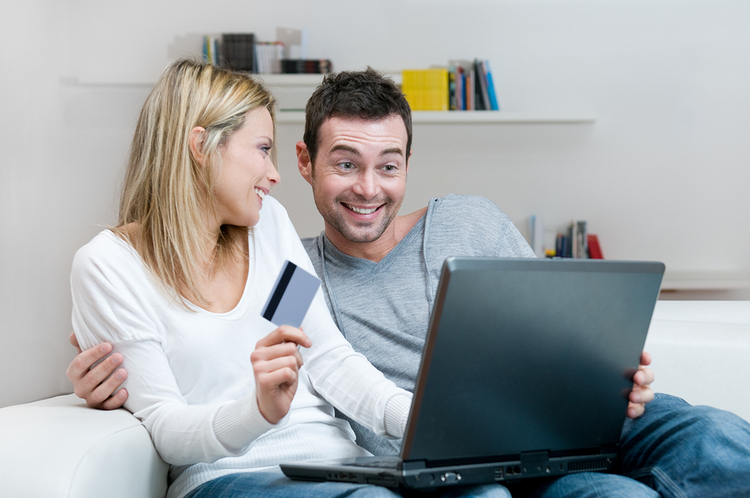 A couple shopping online using a laptop.