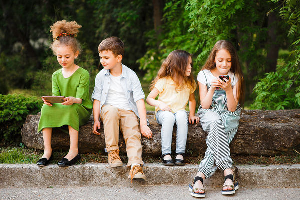 Group of young teens sitting outside looking at their phones.