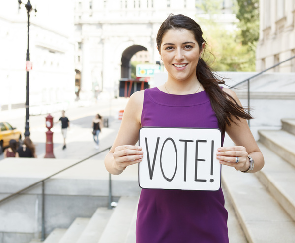 Woman holding a Vote sign.