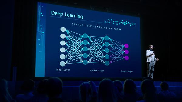 Speaker presenting information on deep learning.
