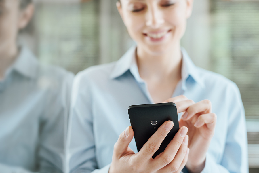 Image of woman using smartphone. Attractive website and mobile design paired with effective inbound marketing strategies can help drive conversions.