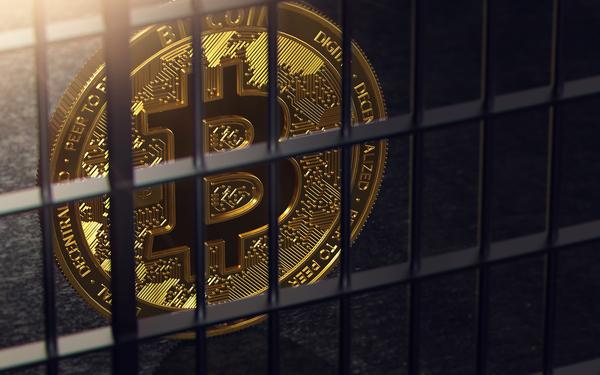 Gold coin inside jail bars.