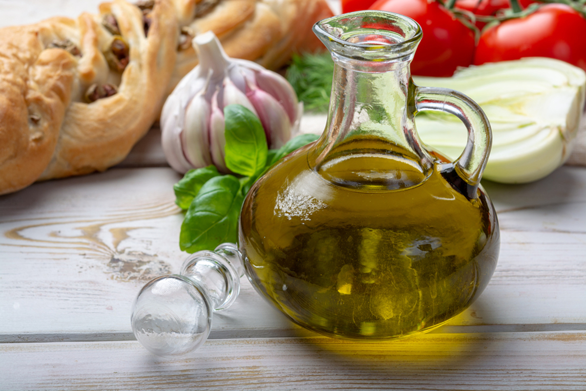 Glass container of oil on a table with fresh bread and vegetables.