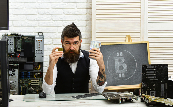 Computer technician holding cash in one hand and computer chip in the other.