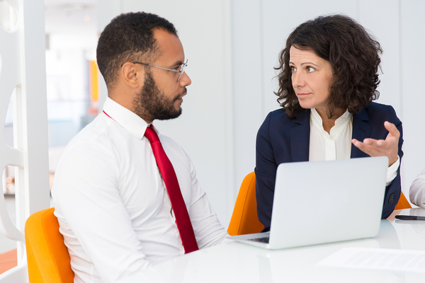 Two people having a conversation in front of a laptop.