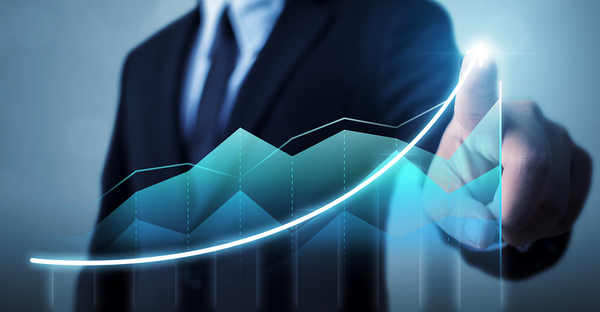 Man in a business suit pointing to an upward growing bar graph.