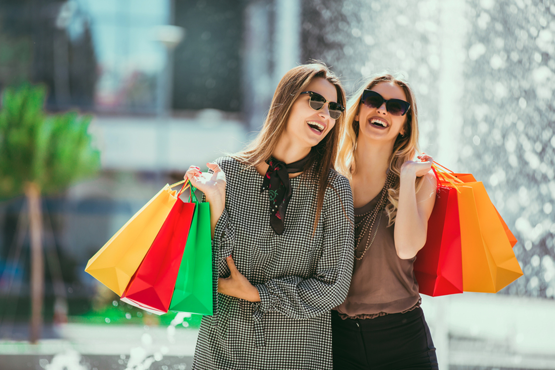 Two women smiling with shopping bags.