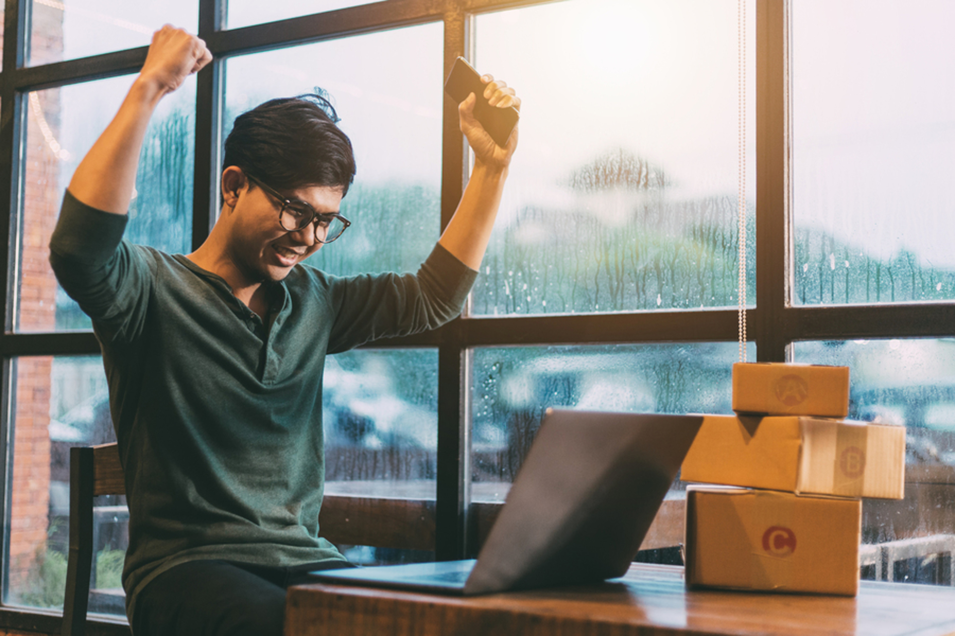 Man holding his arms up in triumph while sitting at a table with a laptop.