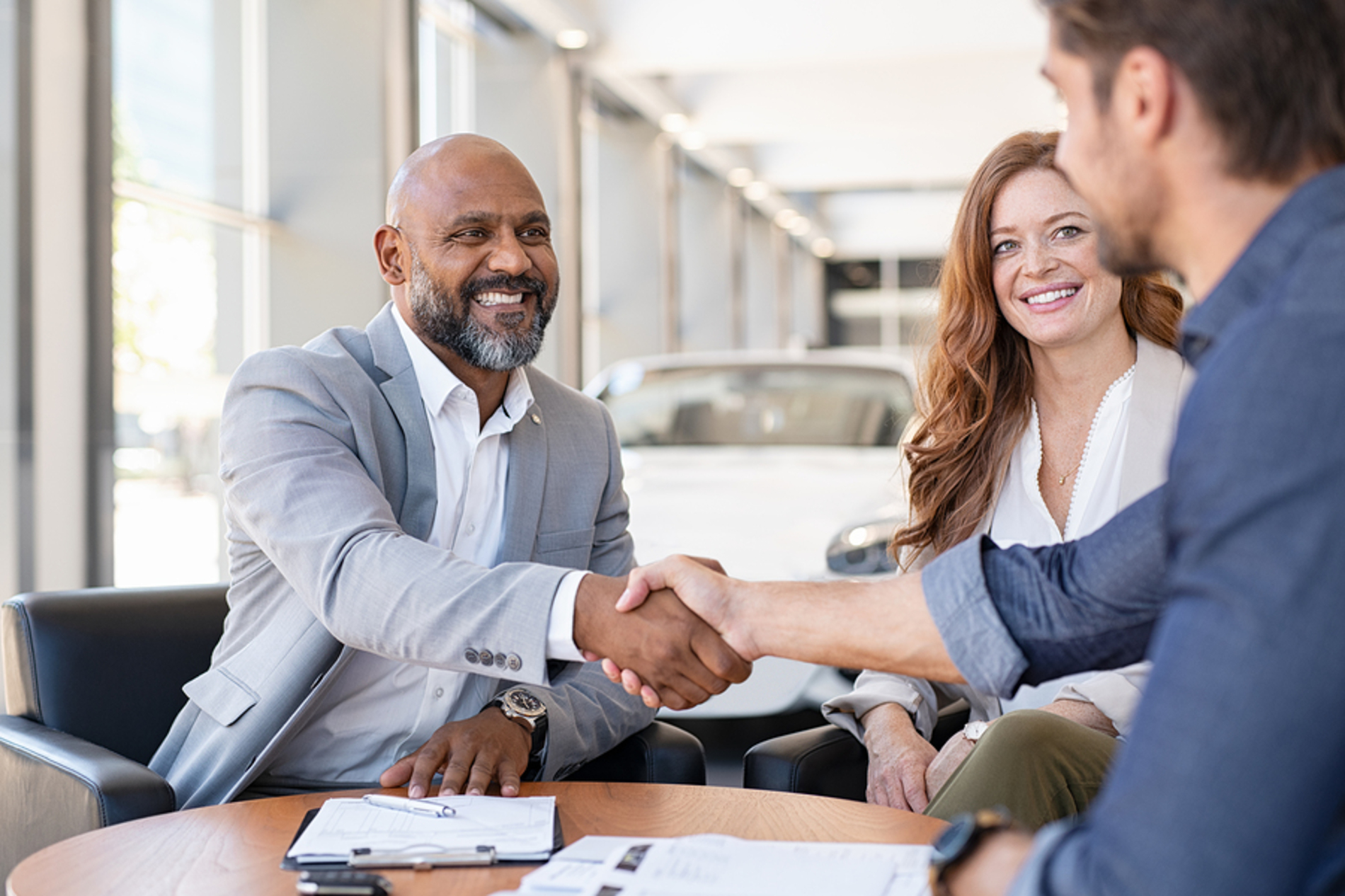 Man shaking hands with a car dealer.