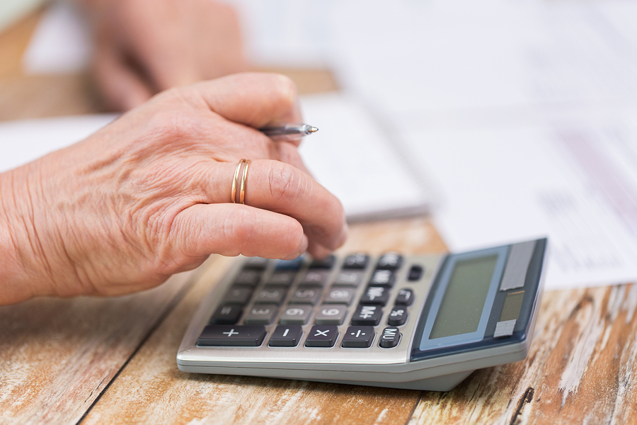 small business cost savings hand working on calculator