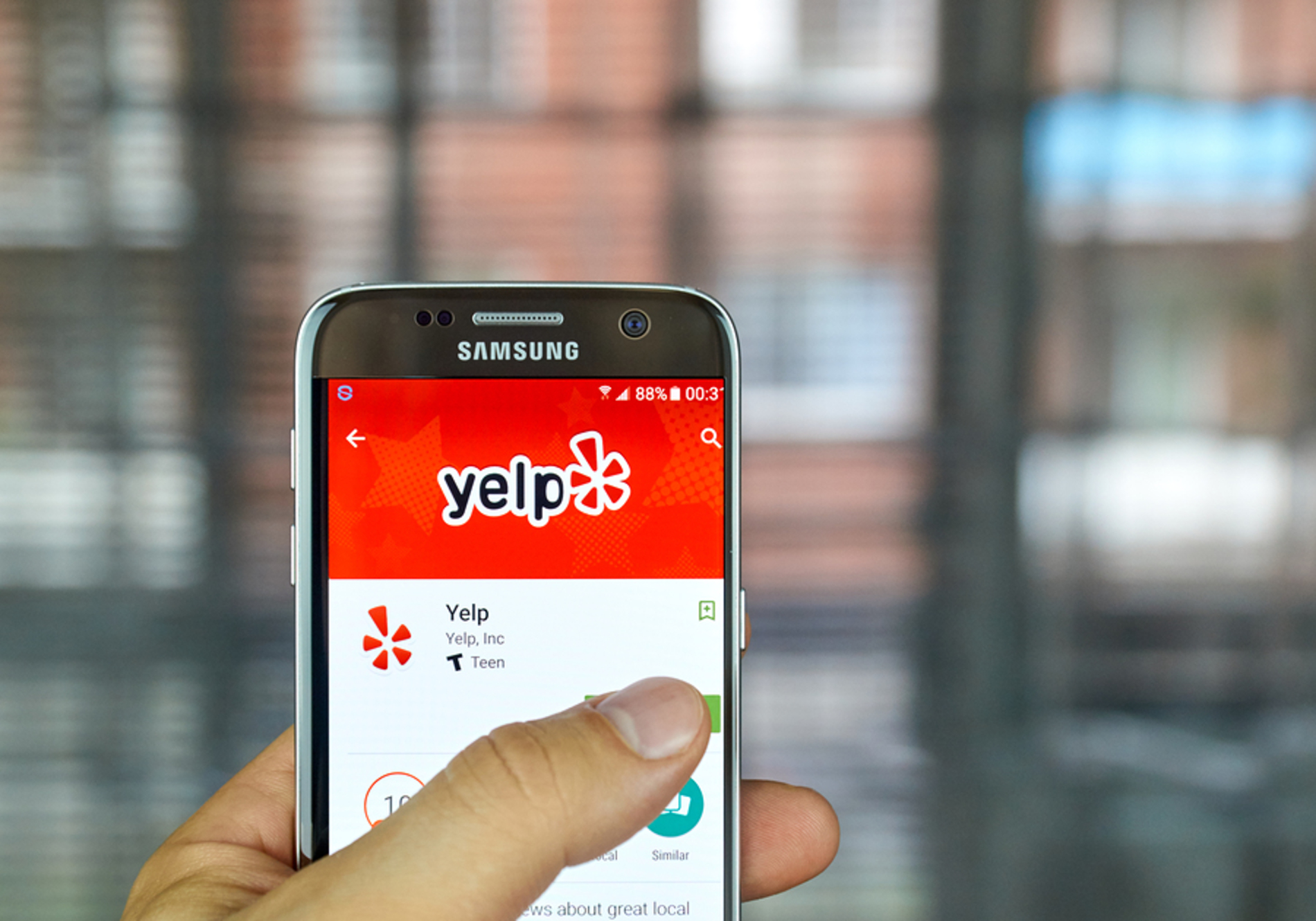 Mobile phone with the yelp app on display.