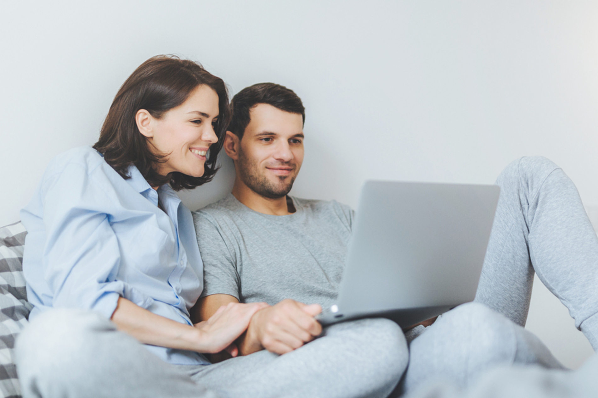 Couple smiling while looking at a laptop.