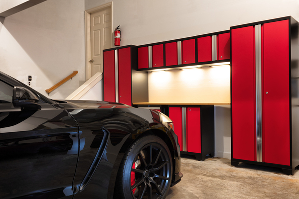 Garage with red cabinets and black sports car.