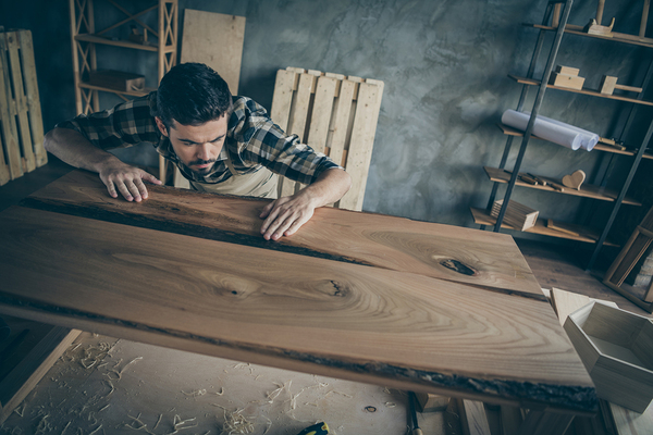 Man creating an wooden cabinet with planks of wood.