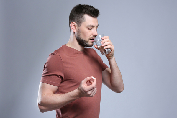 Man taking an ED drug with a glass of water