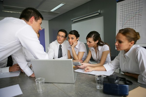 Group of colleagues discussing information on a laptop and documents.