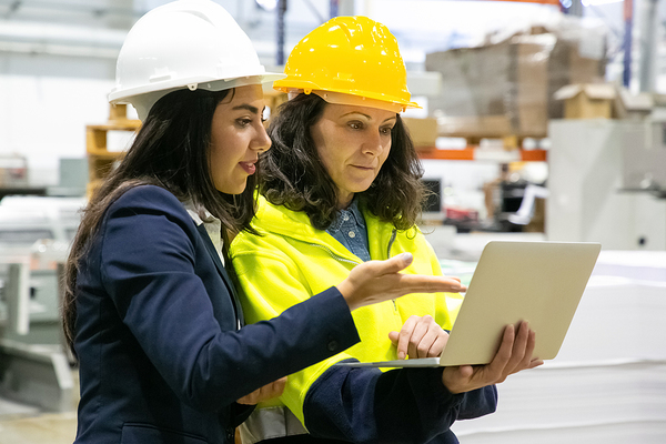 Two women wearing hard hats discussing information on a laptop.