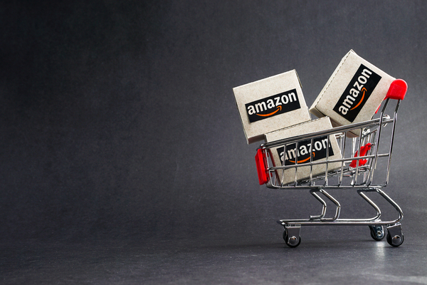 Miniature shopping cart filled with amazon boxes.