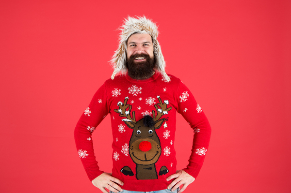 Smiling man wearing a reindeer sweater.
