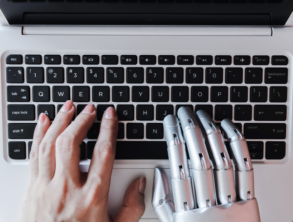 Human left hand and robotic right hand typing on a laptop computer.