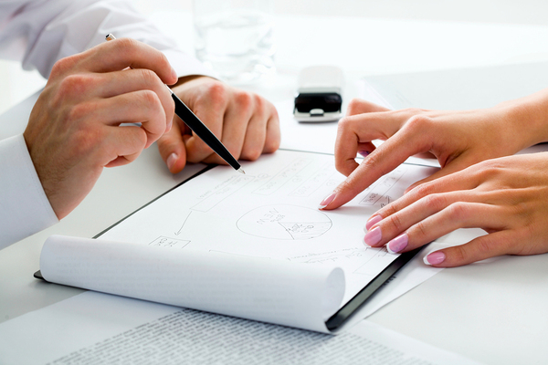 man and woman reviewing a piece of paper (just hands)