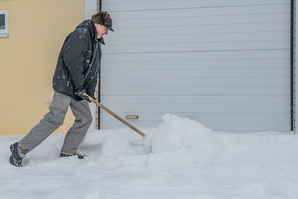Man shoveling in front of a garage.