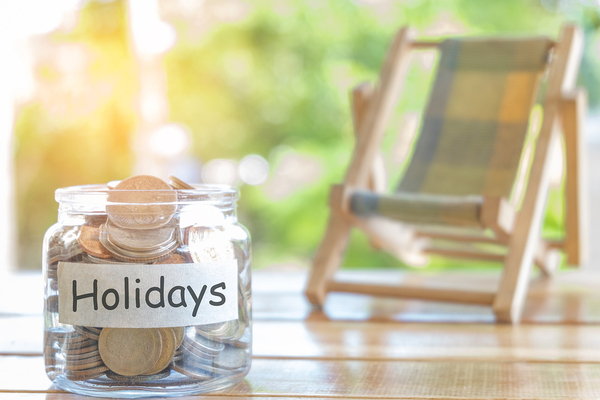Glass jar labeled Holidays filled with coins.